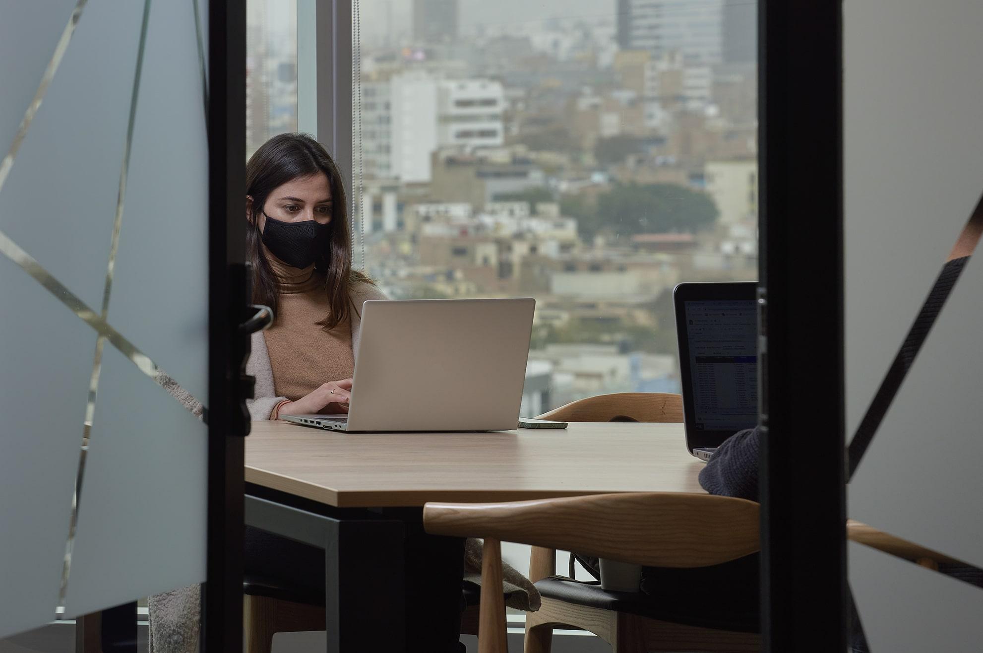 mujer trabajando en una oficina satelite usando mascarilla