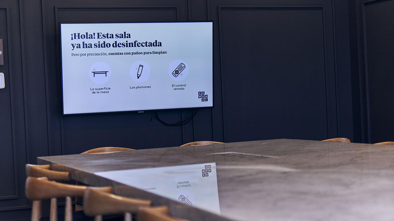 sala de reuniones con televisor mostrando un mensaje de que la sala ha sido desinfectada